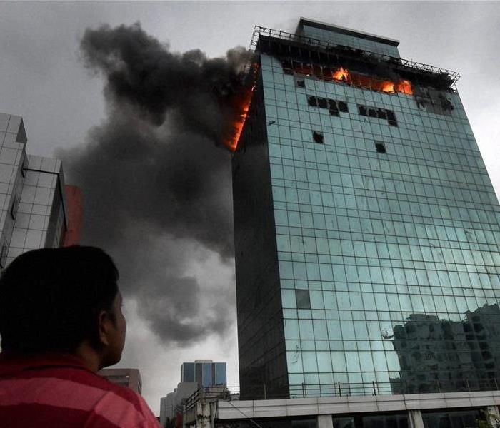 Man looking up at corporate building on fire